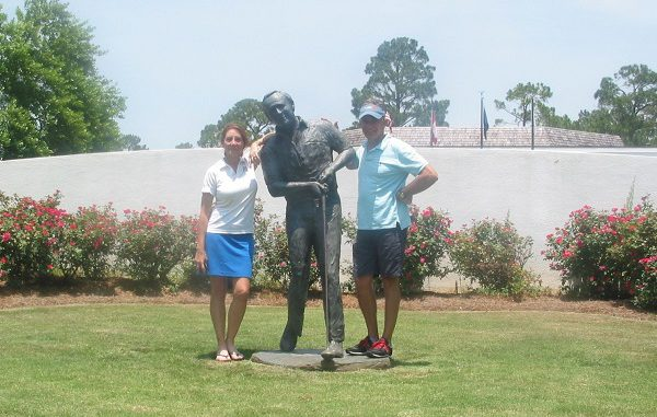 couple posing in front of golf statue