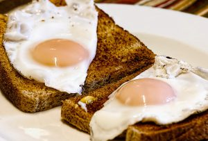 Two slices of toast with sunny side up eggs.